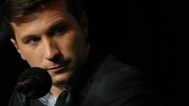 Gabriel Nadeau-Dubois parle dans un micro sur fond noir.