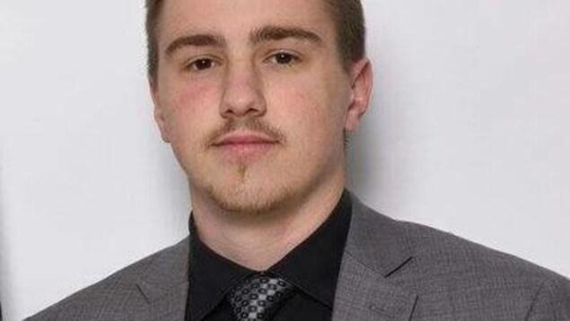 Le jeune homme en complet et cravatte est posé devant un mur blanc