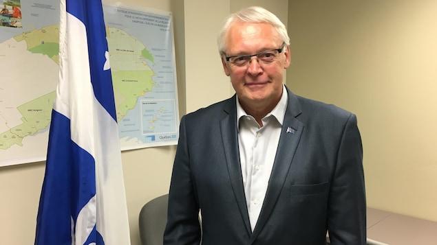 Le député indépendant de Gaspé, Gaétan Lelièvre sourit à la caméra, debout près d'un drapeau du Québec.