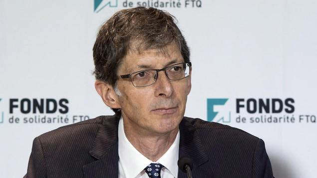 Un homme répond aux questions de journalistes lors d'une conférence de presse.