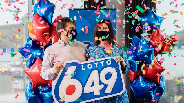 Le couple sous les confettis tient une affiche de la loterie 6/49 .