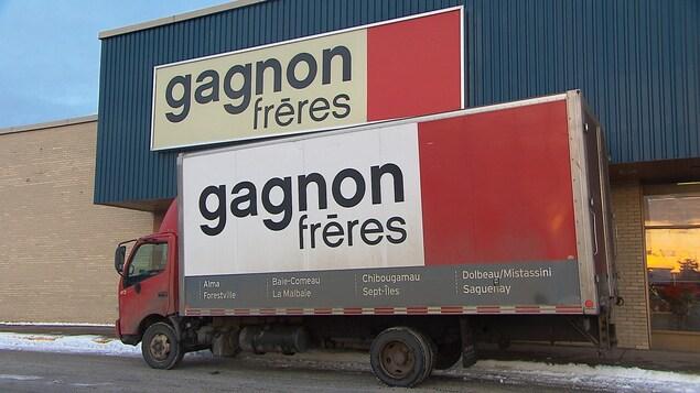 Un camion de l'entreprise est stationné devant la porte du magasin. Les deux ont le logo de Gagnon Frères.