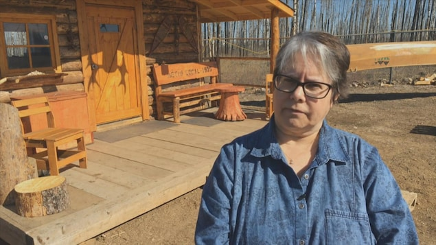 Gail Gallupe se tient devant une maison en bois.