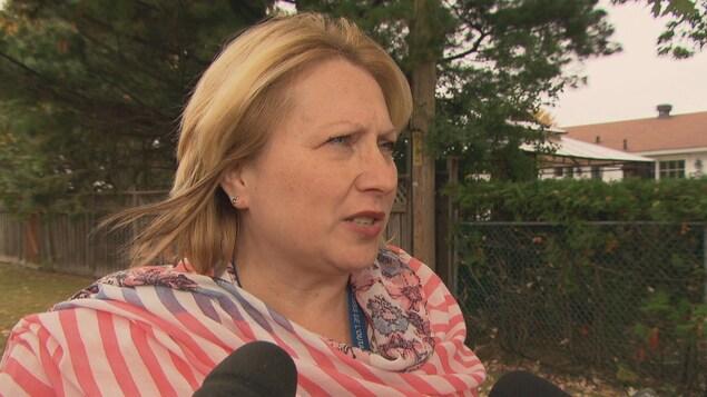 La femme est interviewée devant une clôture