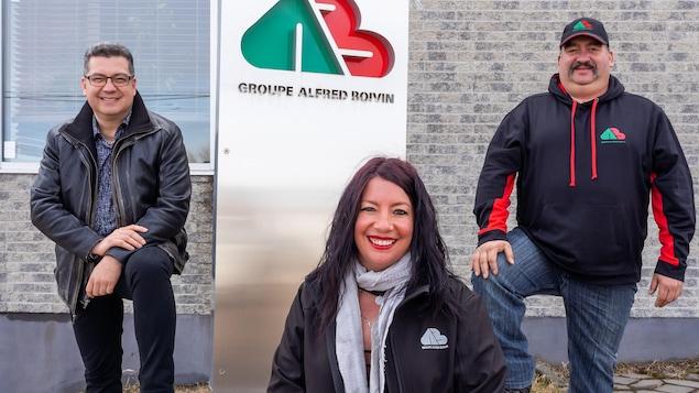 Trois personnes posent devant une affiche d'entreprise.