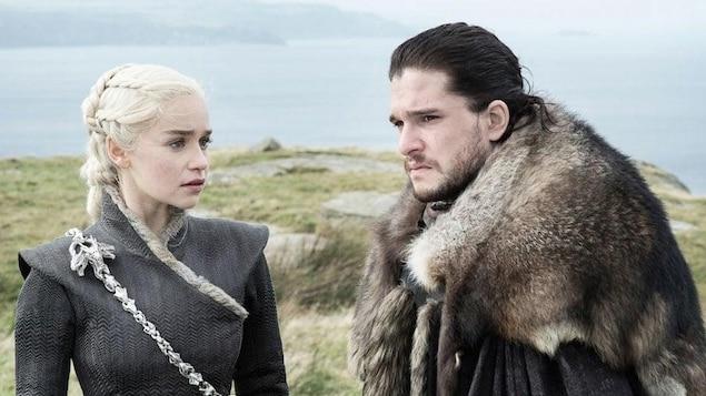 Les personnages Daenerys Targaryen et Jon Snow, vêtus d'habits à l'allure médiévale, se tiennent devant une étendue d'eau.