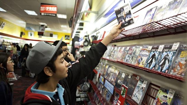 Un jeune prend un jeu sur une tablette d'un magasin de jeux vidéo.