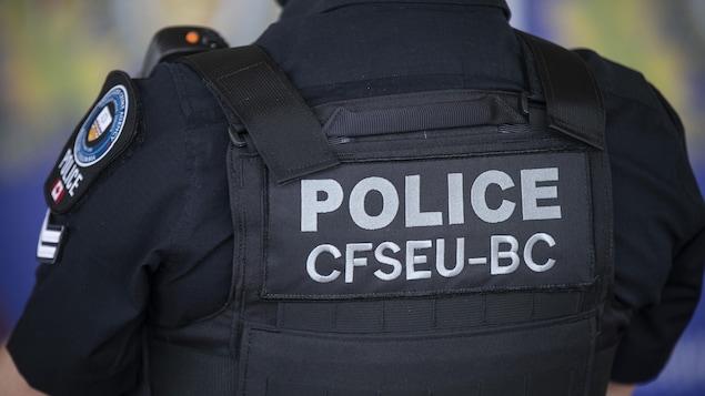 Un agent de l'Unité mixte d'enquête sur le crime organisé de dos lors d'une conférence de presse le 10 mai 2021.
