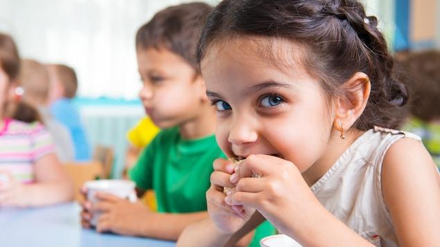 Des enfants assis à une table mangent une collation en buvant un verre de lait.