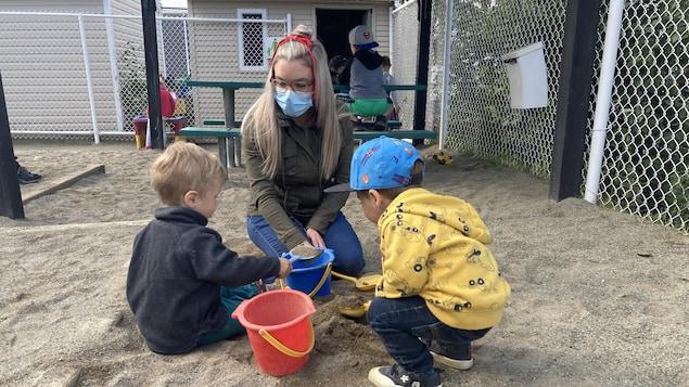 Une éducatrice joue dans le sable avec des enfants dans la cour d'une garderie de Rouyn-Noranda.
