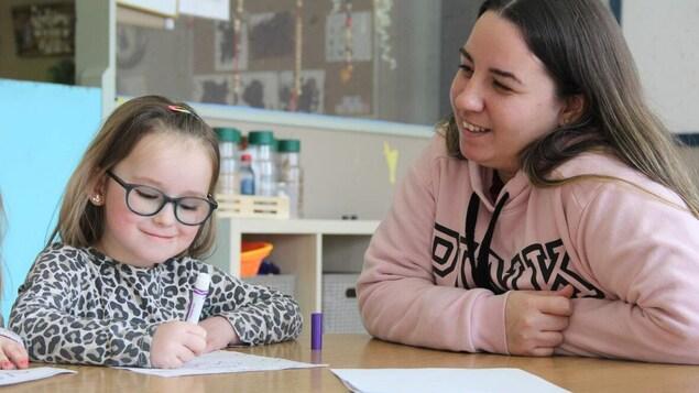 Une jeune femme regarde une fille qui dessine.