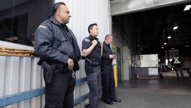 3 gardes de sécurités se tiennent dos à un mur de l'aéroport