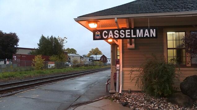Un écriteau suspendu à la gare, le long des rails, indique l'arrêt pour Casselman.