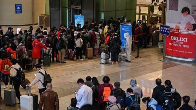 Des passagers font la file dans une gare.