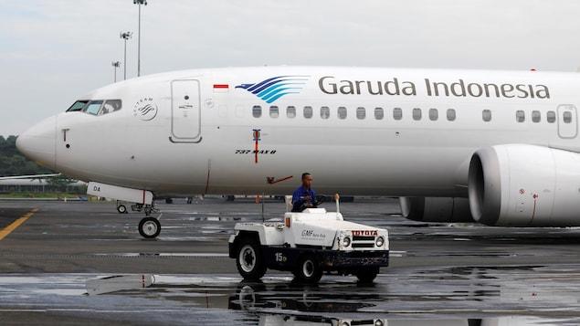 Un employé passe près d'un des avions de Garuda Indonesia dans un aéroport.