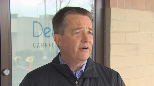 Un homme aux cheveux grisonnants parle devant la devanture d'un magasin Delta 9.