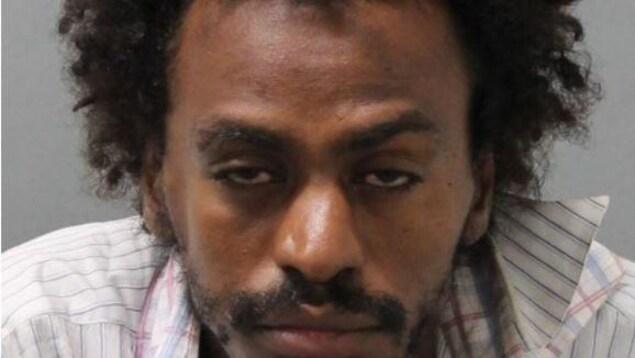 Portrait d'un homme noir aux cheveux bouclés avec le regard absent.