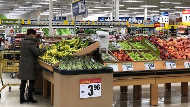 Une femme en train de choisir des bananes dans un présentoir chez Maxi.