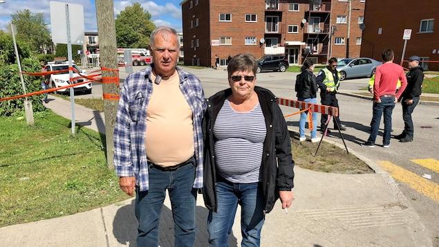 Un couple pose au coin d'une rue, un policier parle avec des citoyens derrière.