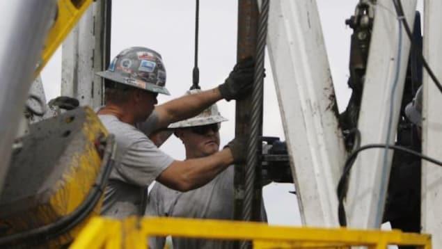Deux travailleurs travaillent sur un forage gazier.