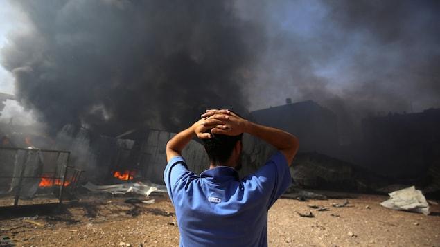 Un homme, avec les mains sur la tête, est debout face à un nuage de fumée noire.