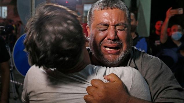 Un homme pleure en tenant dans ses bras un jeune homme dont on ne voit pas le visage.