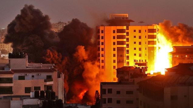 Du feu et de la fumée noire se dégagent d'un quartier.