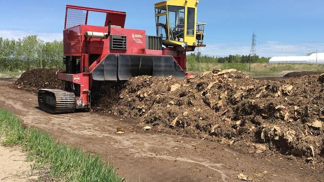 Une machine rouge retourne du compost dans un champs.