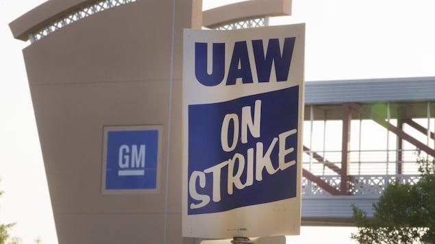 Une affiche du syndicat sur laquelle il est écrit «En grève» devant un bâtiment de General Motors.