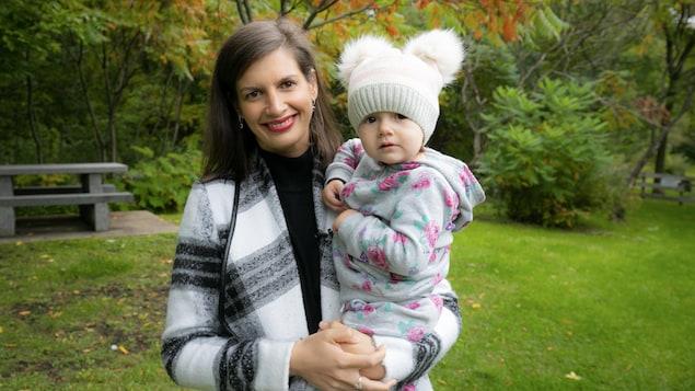 Geneviève Guilbault tient sa fille dans ses bras, souriante
