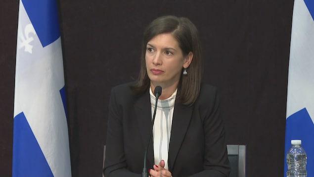 Geneviève Guilbault lors d'un point de presse. Elle est assise à une table, derrière un micro, entourée de deux fleurdelisés.