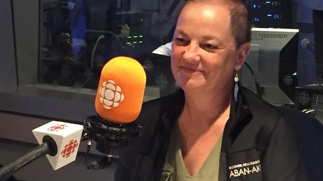 Geneviève Treyvaud, souriante, devant un micro, dans les studios de Radio-Canada Mauricie.