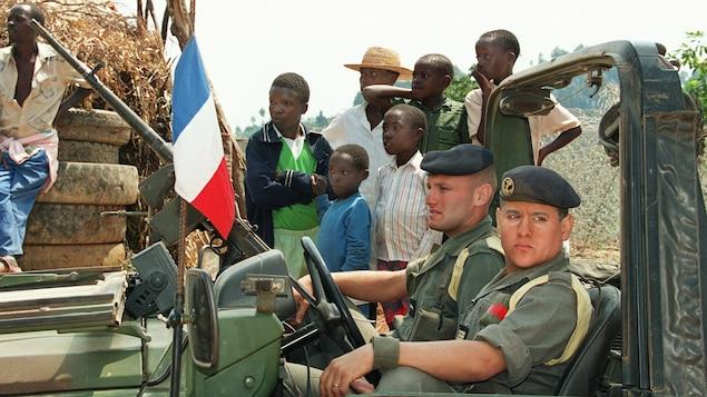 Deux soldats sont assis dans un véhicule militaire entourés de Rwandais.