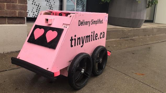 Un petit robot rose pâle avec de gros pneus sur un trottoir à Toronto.