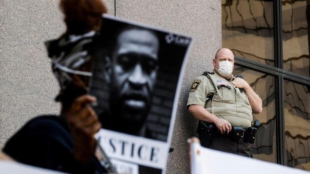 Un policier masqué regarde un manifestant.