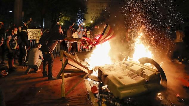 Des manifestants devant des barrières en feu.