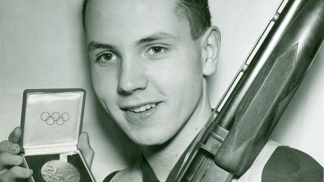 Un homme avec une médaille olympique et un fusil.