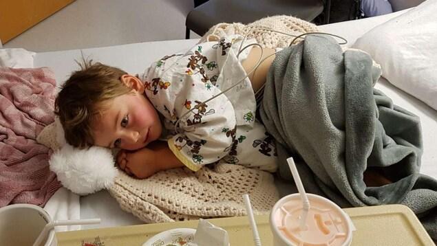 Un garçon de 4 ans allongé dans un lit d'hôpital.