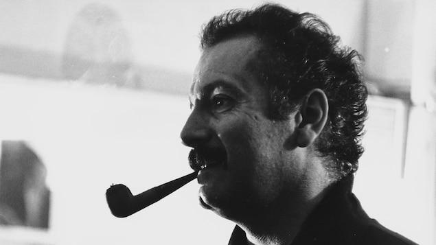 Georges Brassens est de profil avec une pipe à la bouche.