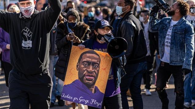 Les manifestants défilent en brandissant des pancartes à l'effigie de George Floyd