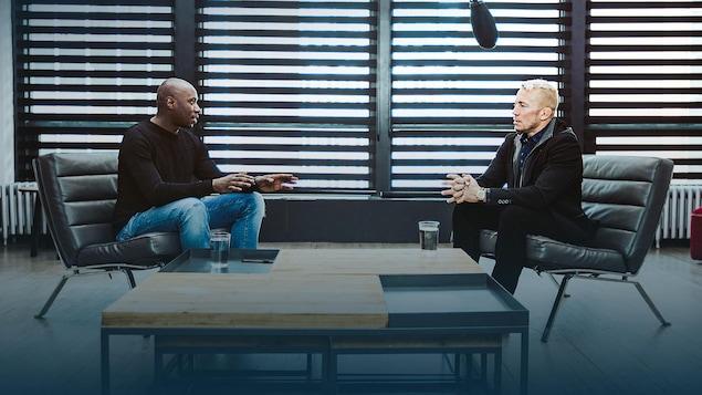 Les deux hommes sont assis face à face et discutent.
