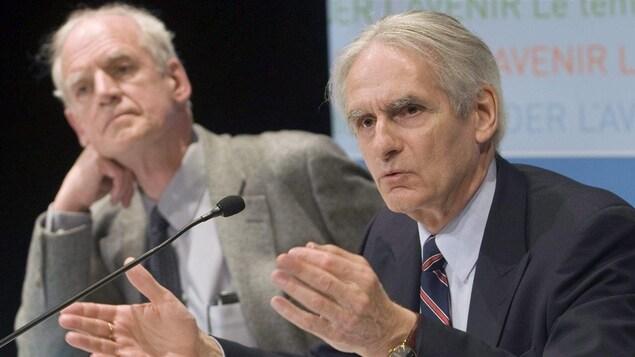 Charles Taylor et Gérard Bouchard assis derrière une table lors du dévoilement de leur rapport de la commission sur les accommodements raisonnables en mai 2008.