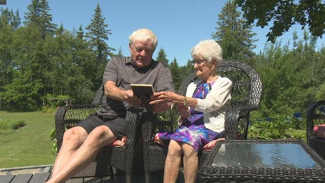 Gérard Cormier et Ernestine McDermott-Derry sur des chaises dans un jardin.