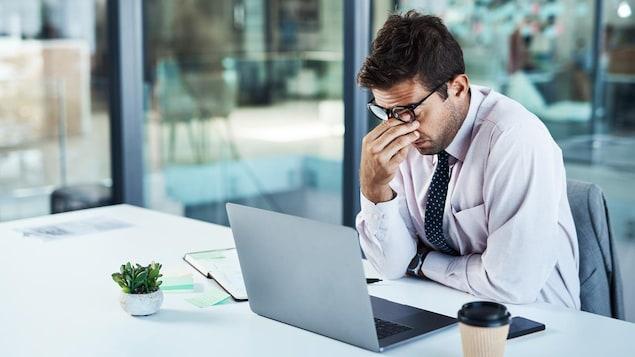 Un homme d'affaires découragé devant son ordinateur.