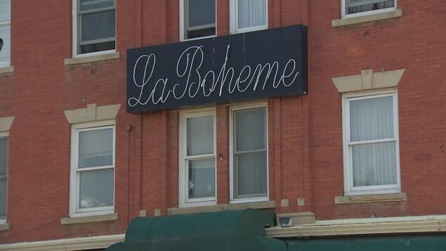 La façade de l'édifice Gibbard est ornée par l'enseigne du café La Bohème.