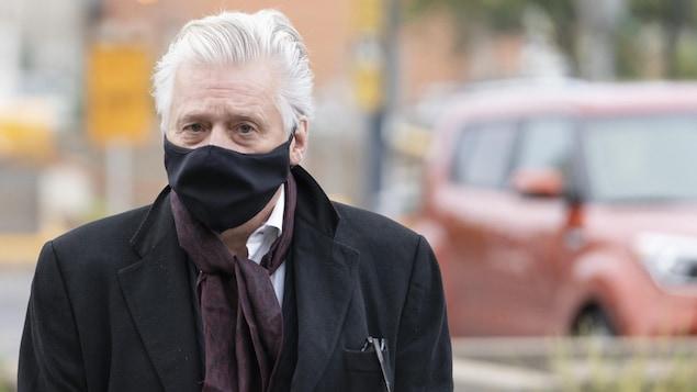 Gilbert Rozon, portant un masque, à l'extérieur du palais de justice de Montréal.