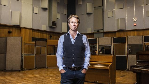 Un homme pose dans un studio d'enregistrement de musique.