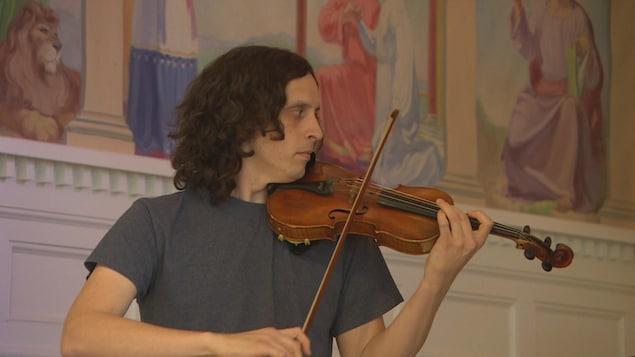 Un homme joue du violon dans une église.