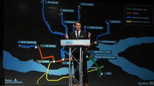 François Bonnardel derrière le podium lors de la conférence de presse avec la carte du Réseau express de la Capitale en arrière plan.