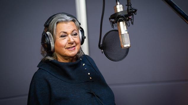 La chanteuse se tient devant un micro, une paire d'écouteurs sur la tête.